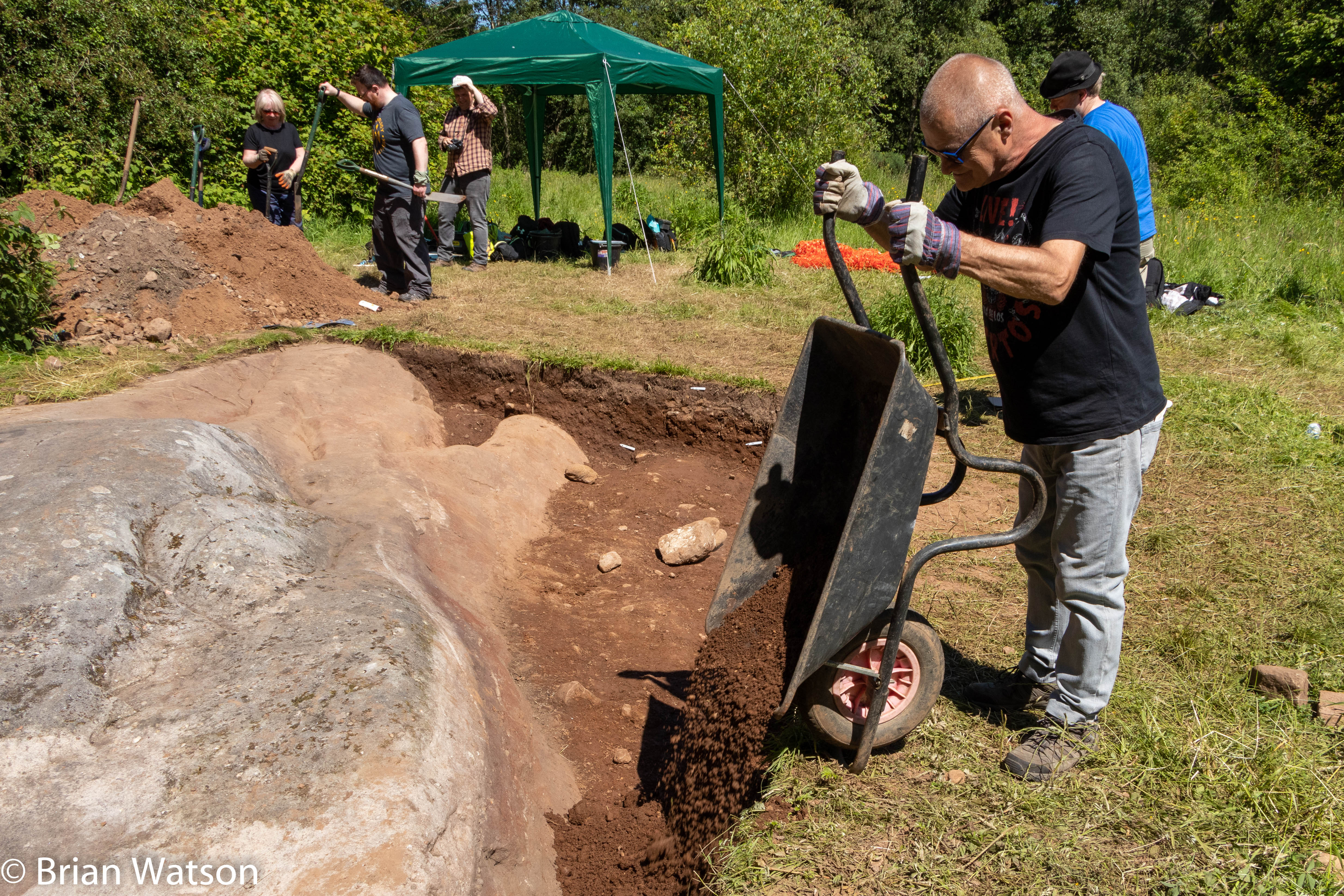 Tipping soil from a wheelbarrow into the trench at the Faifley Rocks excavation.
