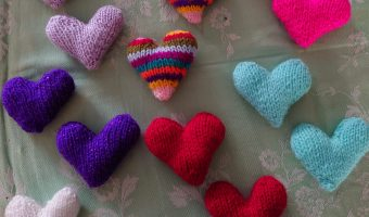 a selection of colourful kntted hearts