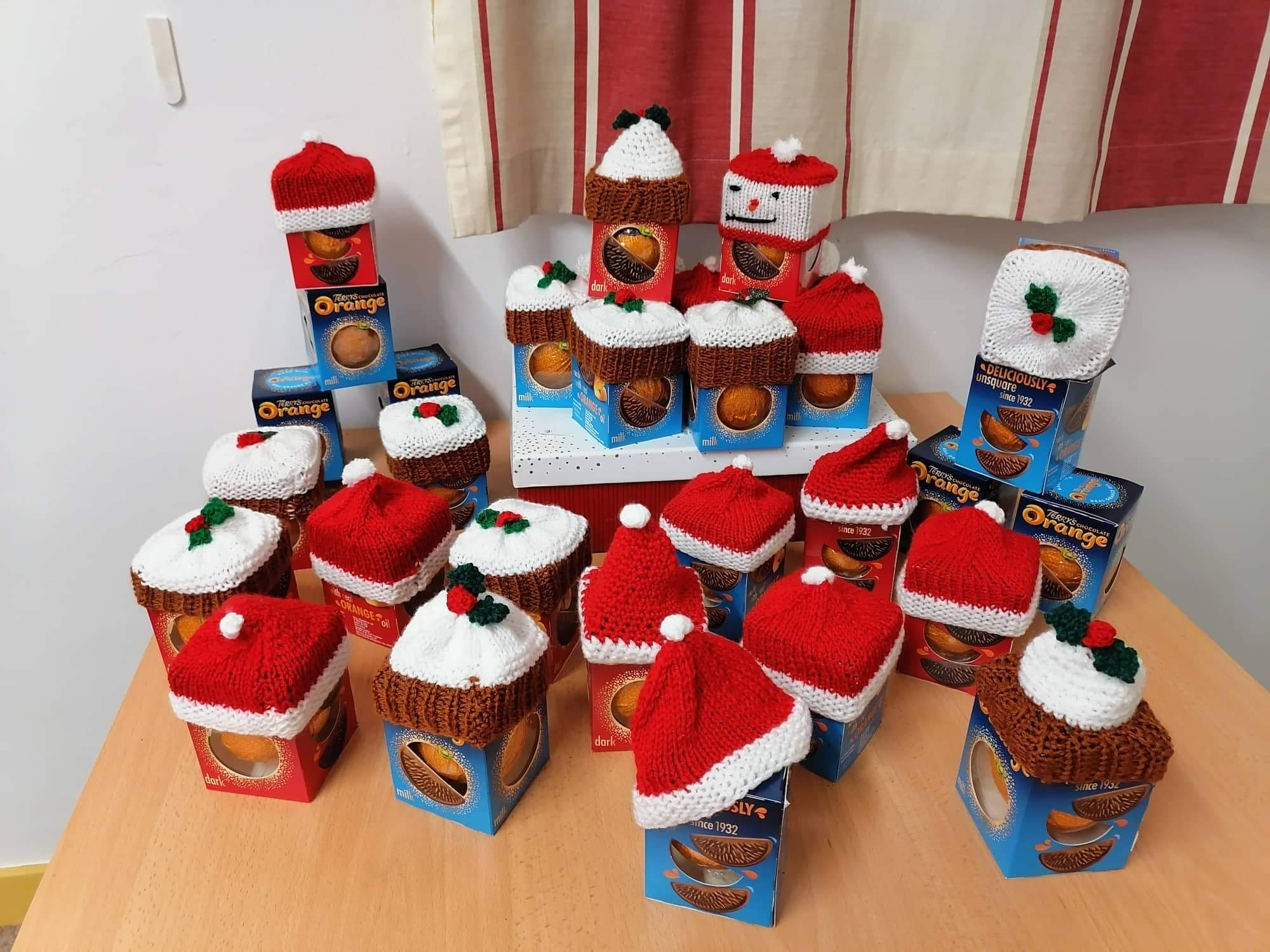 A pile of chocolate oranges with festive knits toppers