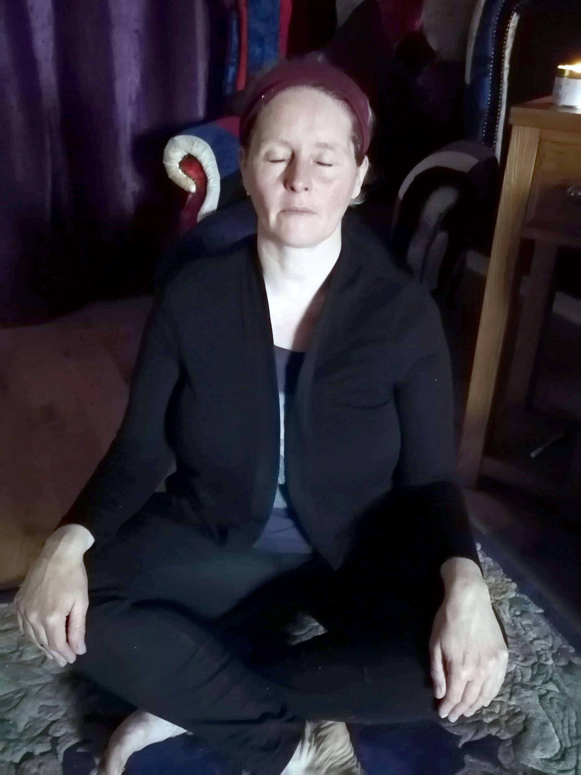 Angela sitting in a mindfulness pose
