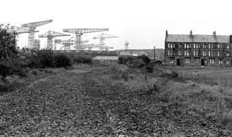 B+W Panoramic image of cranes with old classic-style flats to the right.
