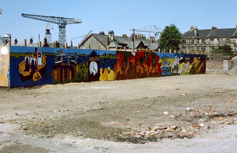 Image of colourful artwork of Clydebank imagery on the wooden fencing on the outskirts of a shipyard, with crane visible in distance.