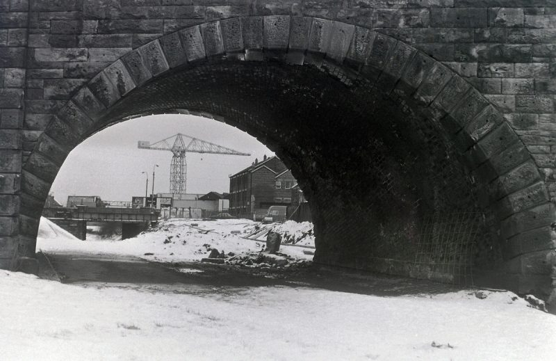 B+W Image of a brick arch-way bridge from underneath, with a crane visible through the arch.
