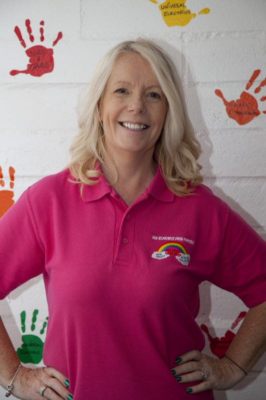 A lady wearing a pink-polo shirt with an OKFP Rainbow logo.