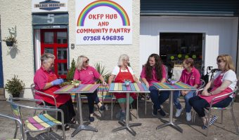 """A group of ladies sitting at a set of outside table and chairs on a sunny day, behind them a sign titled """"OKFP HUB AND COMMUNITY PANTRY"""""""