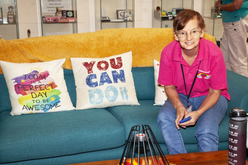 """A woman with an OKFP pink polo-shirt, sitting on a blue couch with cushions that read """"Today is a perfect day to be awesome."""" and """"You can do it."""""""